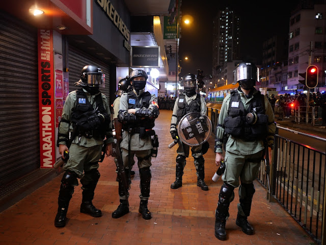 four Hong Kong police officers wearing riot gear — three holding pepper spray canisters
