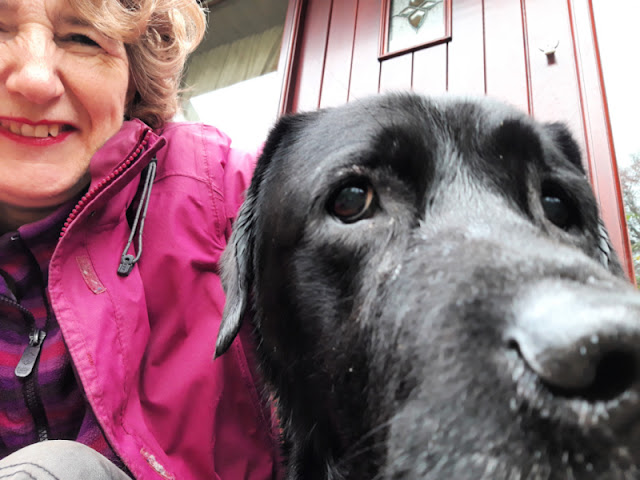 Christine and her black dog.  Christine is wearing a pink coat, the dog is being aloof