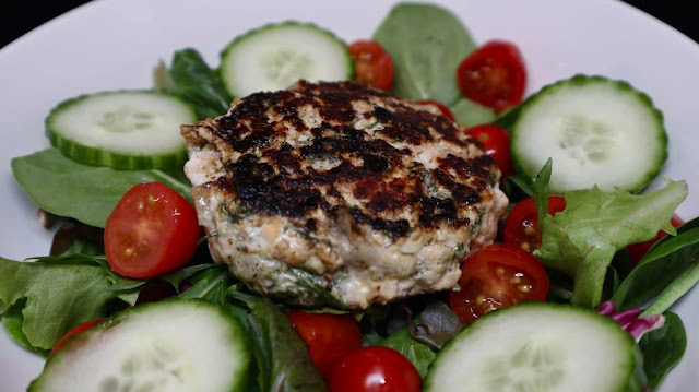 white plate, salmon burger on salad with cucumbers and tomatoes