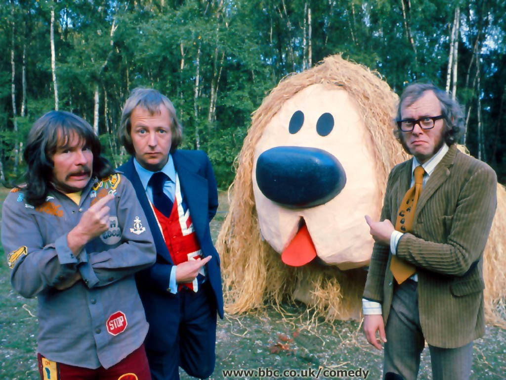 An image showing the three members of The Goodies next to a person in a costume