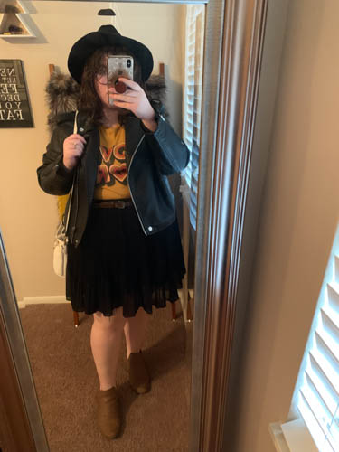 A mirror selfie of an outfit of a black wide brim fedora, a black faux lather jacket, a yellow graphic tee that says Love More, a black pleated skirt, and brown booties.