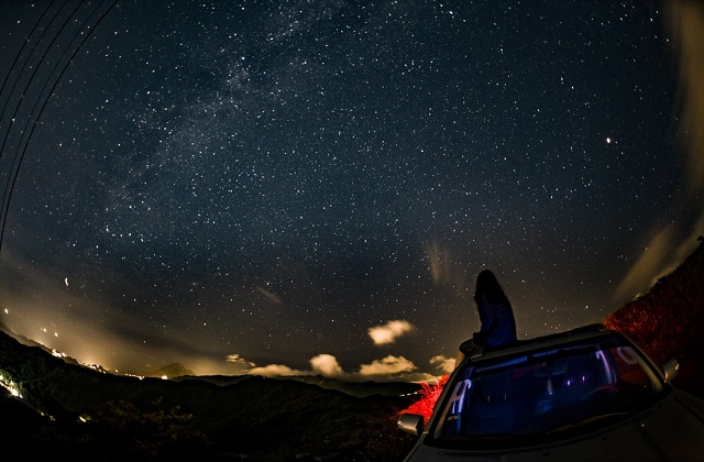 woman sitting on car star gazing beautiful night skies