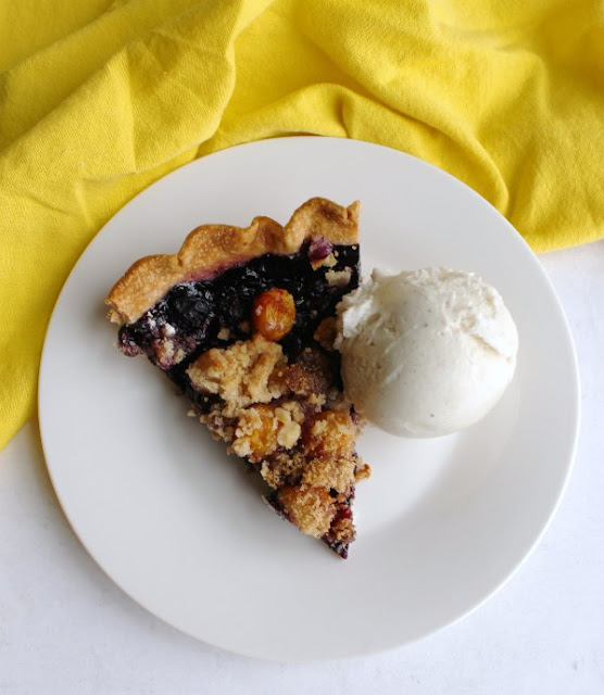 slice of blueberry and goldenberry pie with crumble topping and scoop of ice cream on plate