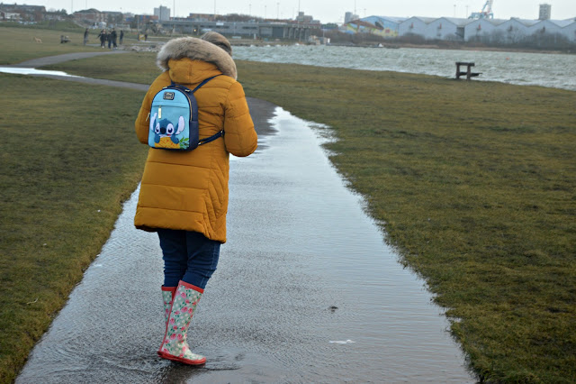 a woman wearing a yellow jacket walking through puddle.