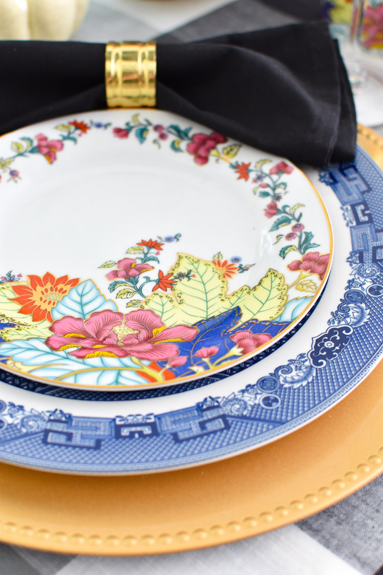 Imperial leaf tobacco leaf plate set on top of a blue willow dinner plate and a gold charger. Such a beautiful chinoiserie inspired table setting and decor.