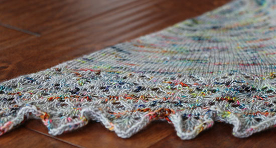 Details of wool hand knit lace shawlette edge in gray with colorful flecks on dark wood.