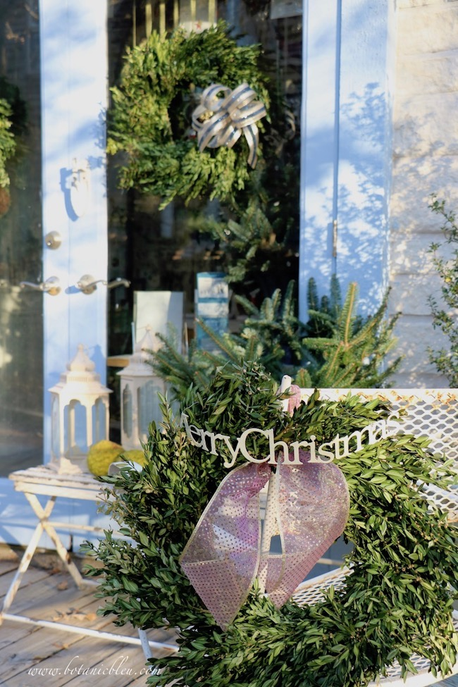 Wired edge sheer ribbons provide sparkle to the French Country Christmas garden shed's exterior decor