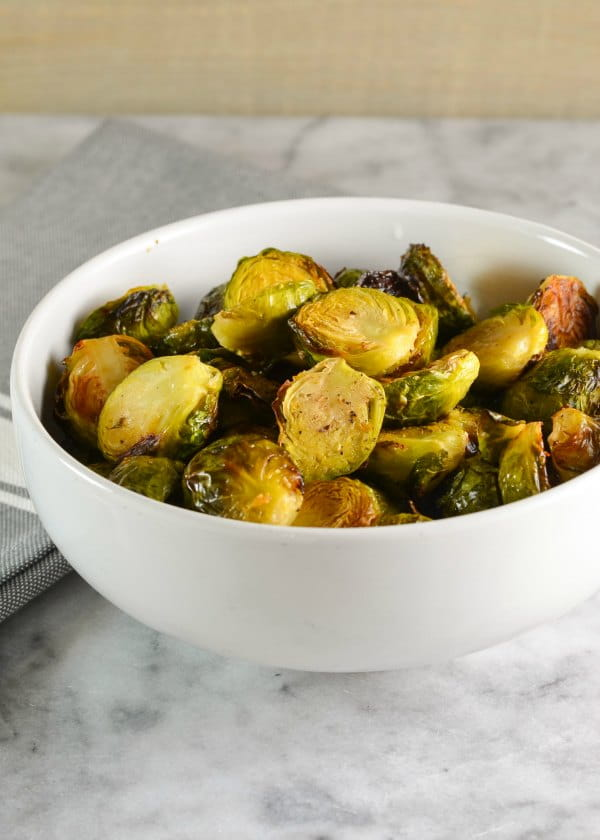 Roasted Brussels Sprouts with Garlic recipe in a bowl. A great side dish for Thanksgiving and Christmas dinner. Easy to make and a favorite roasted vegetable from Serena Bakes Simply From Scratch.