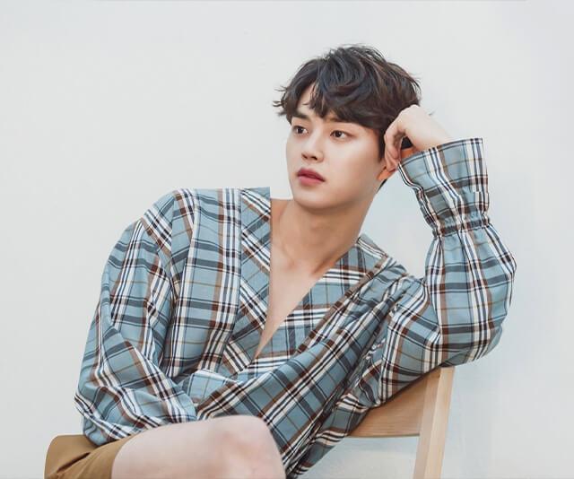 o ator song kang sentando em uma cadeira