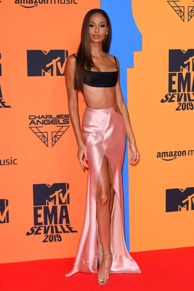 Supermodel Joan Smalls looked sensational in a pink high waisted midi skirt and black bralette