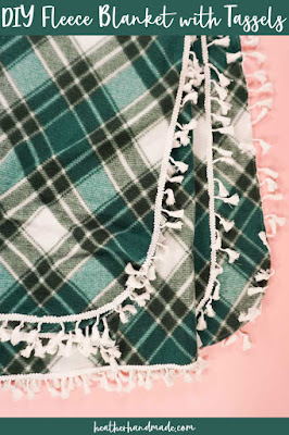 green plaid fleece blanket with tassels.