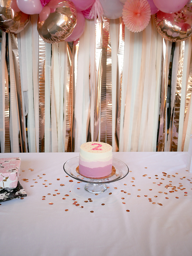 Decorations for a toddler girl's birthday party, blush pink and gold balloon arch and streamers
