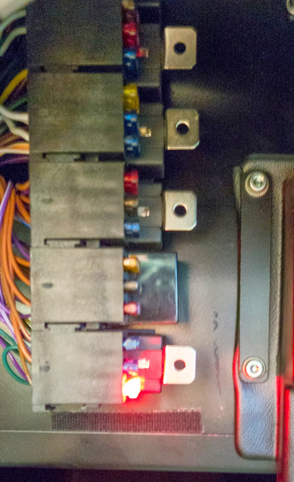 Blown 5 amp LED blade fuse illuminating fuse box.