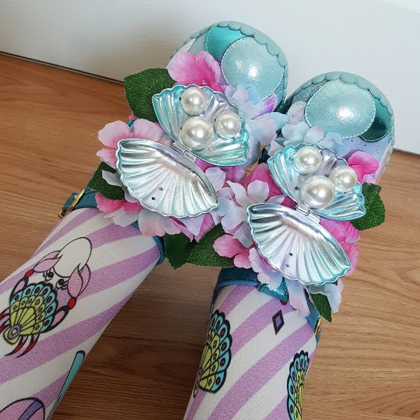 close up of artificial flowers, metal shell and large pearl detail on shoes