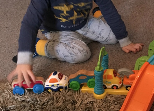 Traffic-Jams-and-Trumpets-toddler-with-cars-lined-up