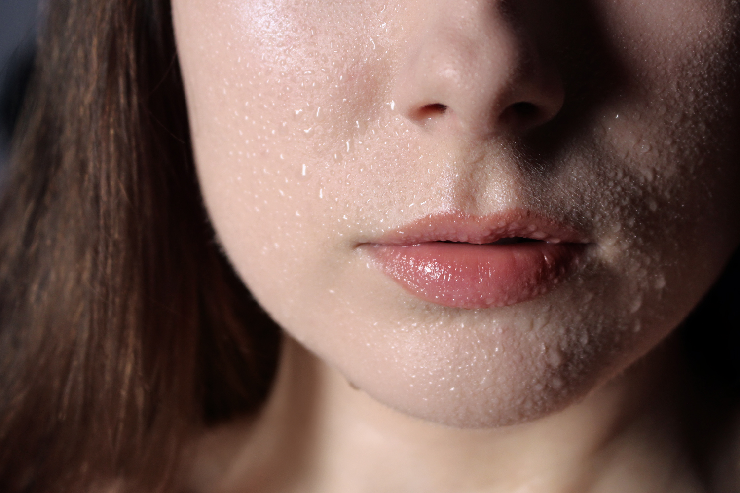 a closeup of a woman's chin with water droplets all over the skin