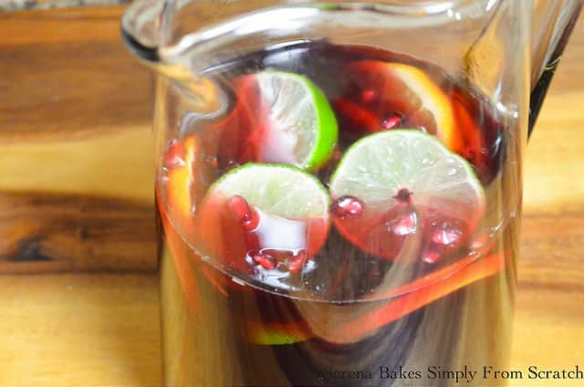 Red Wine Sangria recipe. Merlot Wine, Pomegranate Juice, White Rum, Pomegranate Seeds, Orange Slices, Lime Slices, and Ginger Beer in a pitcher.
