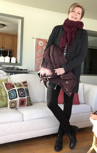 woman in black leggings, charcoal sweater, burgundy scarf, holding a burgundy down coat