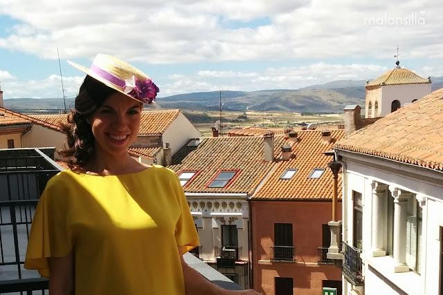 Invitada boda con vestido amarillo mostaza de Zara, sandalias lila, bolso abanico fucsia y canotier de copa baja en color malva y rosa