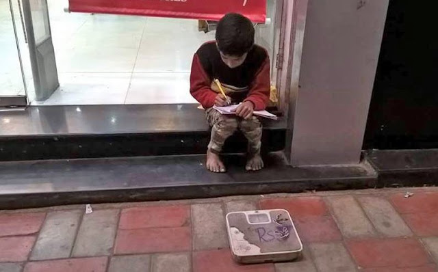 A photo of a boy sitting next to a weighing machine and studying on a road at Kamala Nagar, New Delhi, has gone viral.   The photo is accompanied by a caption which says if you go to Kamala Nagar, meet Gautam, use his scale to weigh yourself and give him some money.   ABP News investigated the photo and found that it was authentic.