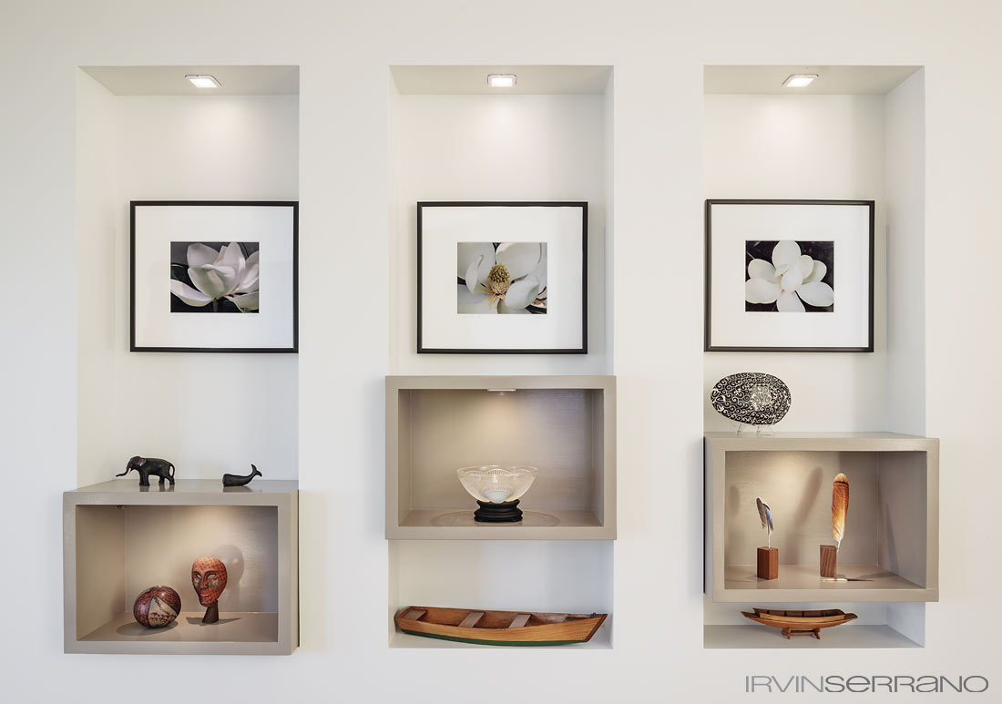 Greenwell designed custom shadow boxes, a Lalique bowl, photographs by Leah Magal, and carved wooden feathers by Gary Yoder adorn a hallway in a residential home in Maine.