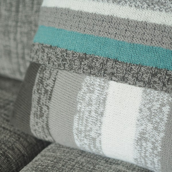 Marled grey section of knitted cushion on grey sofa
