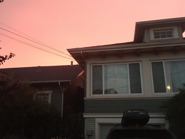 pink smoky, hazy skies over a house