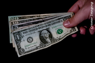 Cramer Imaging's professional quality photograph of a hand holding a one, five, ten, and twenty dollar bill