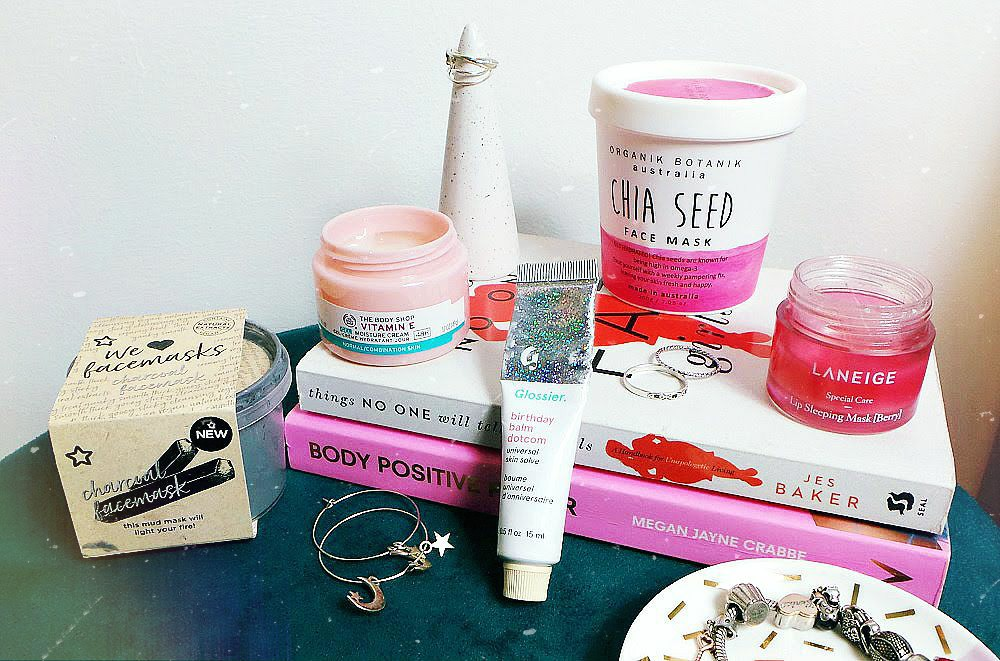 charcoal face mask, chia face mask, lip balm, lip mask and body shop moisturiser are on a stool with an ivy plant, books and jewellery