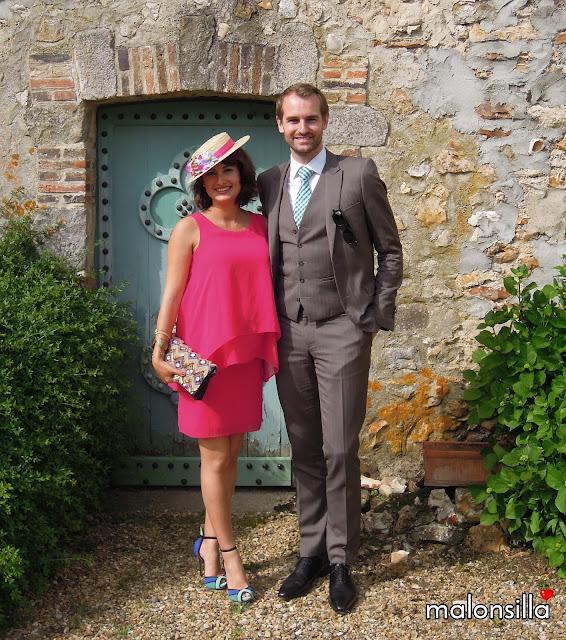 Pareja de invitados boda, vestido fucsia y canotier