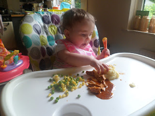 Example of baby led weaning - baby eating Vinaigrette Chicken, cheesy mash, peas and sweetcorn