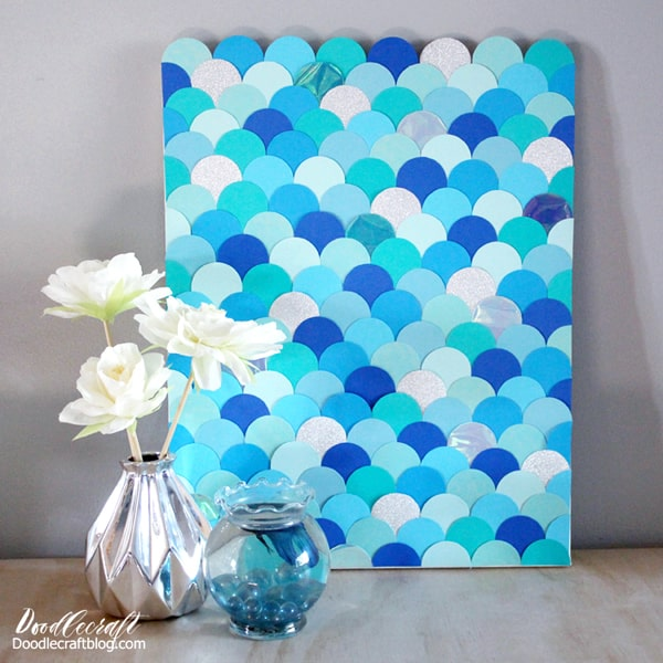 How to make Mermaid fish scales wall art with paper circles in various shades of blue. The different shades of blues, the glitter paper and the iridescent shimmer make this mermaid scale wall art the perfect home decor or party decoration.