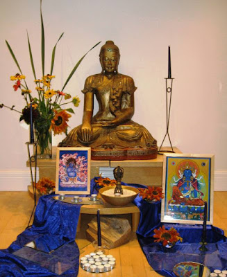Buddha statue surrounded by candles, flowers, symbols and pictures
