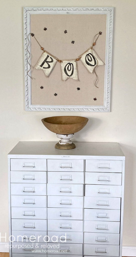 White metal file cabinet with wooden bowl, framed bulletin board and boo banner
