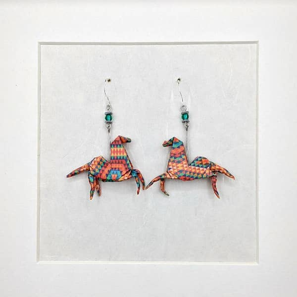 Pair of origami horse earrings made with orange, red, and green patterned paper