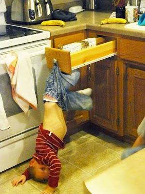 Niño travieso colgando en la cocina.