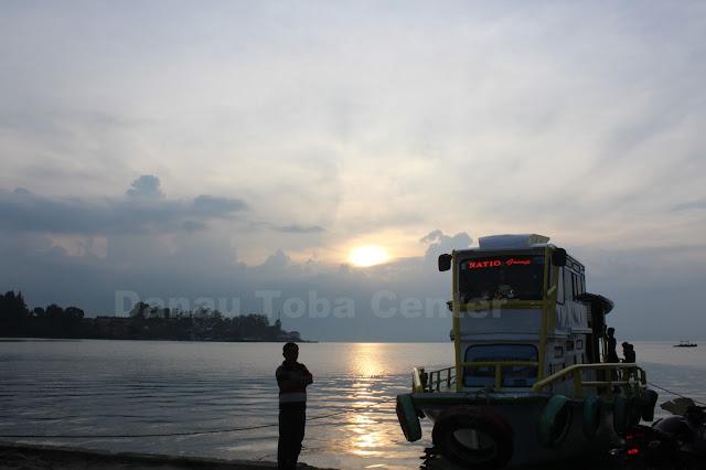 Seorang laki-laki menyaksikan terbenamnya Matahari di Danau Toba, dengan kapal motor penumpang di pelabuhan Danau Toba Parapat.  (photo: tagor)