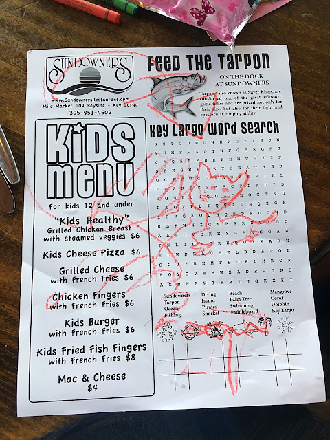 The kid's menu at Sundowners with red crayon drawings on it.