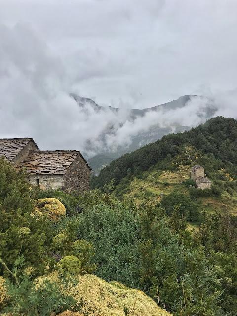 Paisaje de montaña con niebla y nubes a media ladera y dos ermitas