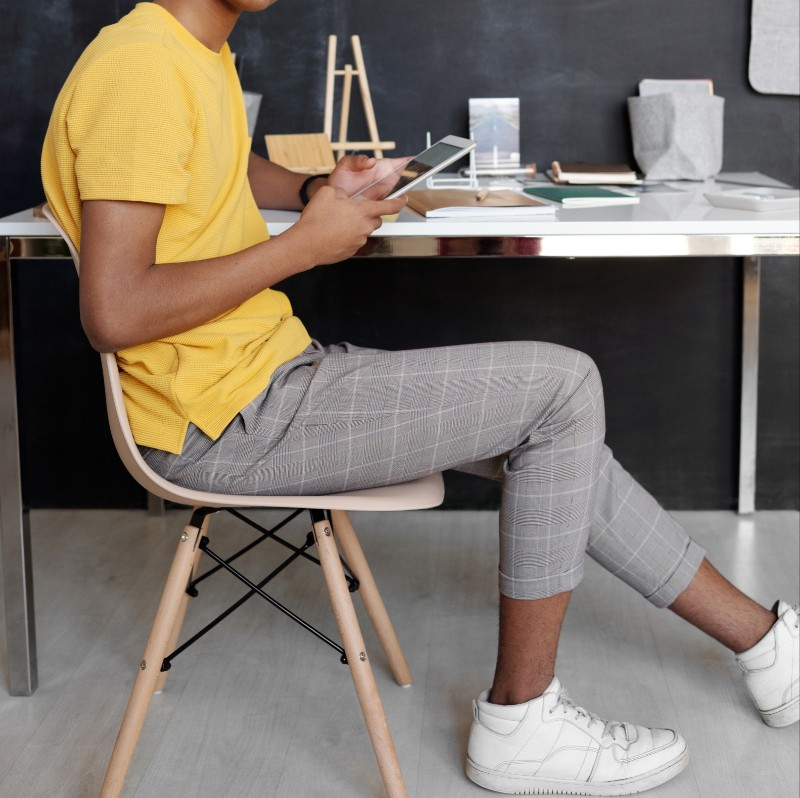 A teen guy sitting on a chair, holding mobile in his hand.