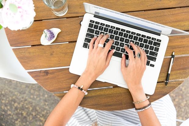 Mãos femininas mexendo em um notebook sobre uma mesa de madeira
