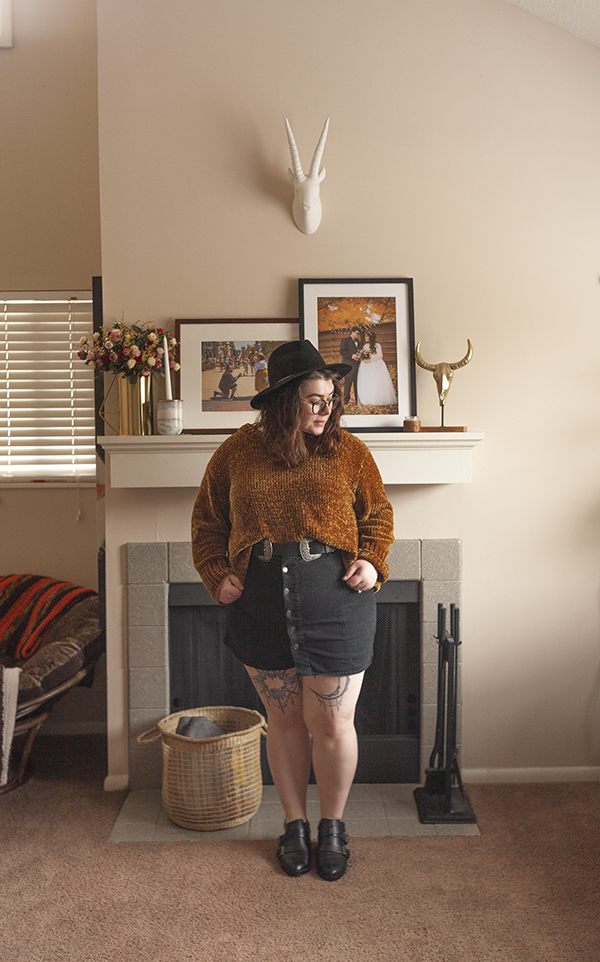 An outfit consisting of a back wide brim fedora, a yellow brown chenille sweater tucked into a black button down skirt and black booties.