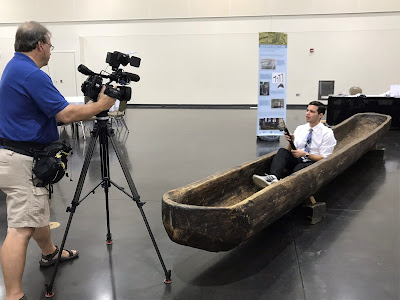News reporter seated in dugout canoe while cameraman records video