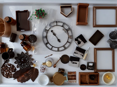 Flat lay of one-twelfth scale modern miniature accessories in brown, copper and rust colours.