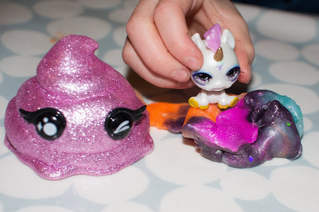 A sparkly pink poop shaped contained with black eyes, multicoloured putty slime and a small white unicorn figure were in our Poopsie Cutie Tootie Surprise drop 2 toy