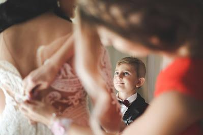 Niño mirando a la novia mientras le terminan de abrochar el vestido
