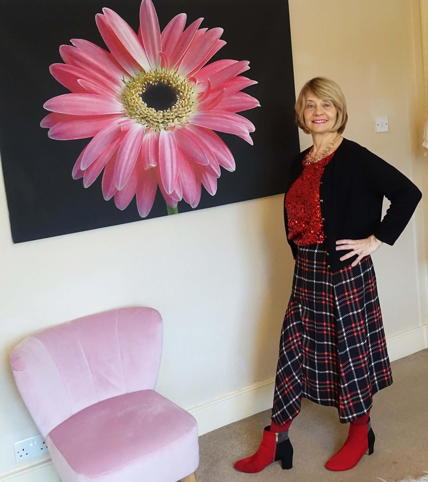 Gail Hanlon from over-50s style blog Is This Mutton in red sequin top, red and black patterned asymmetric skirt and red and black ankle boots