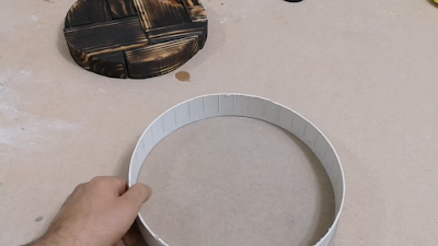 قالب دائري من البلاستيك لصب الإيبوكسي فيه بنفس مقاس الدائرة الخشبية