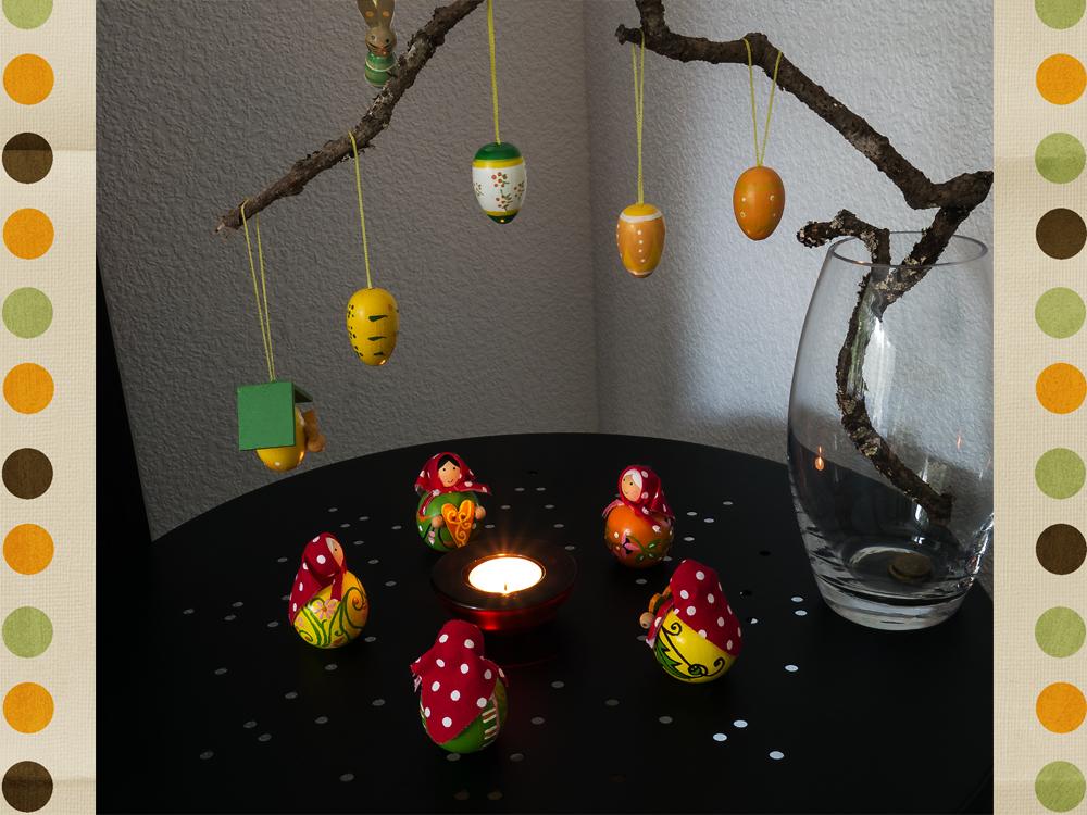Fünf als Osterhexen bemalte Holzfiguren mit Kopftuch stehen um ein brennendes Teelicht unter einem mit Ostereiern dekorierten Zweig