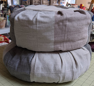 Two round pillows, one stacked on top of the other